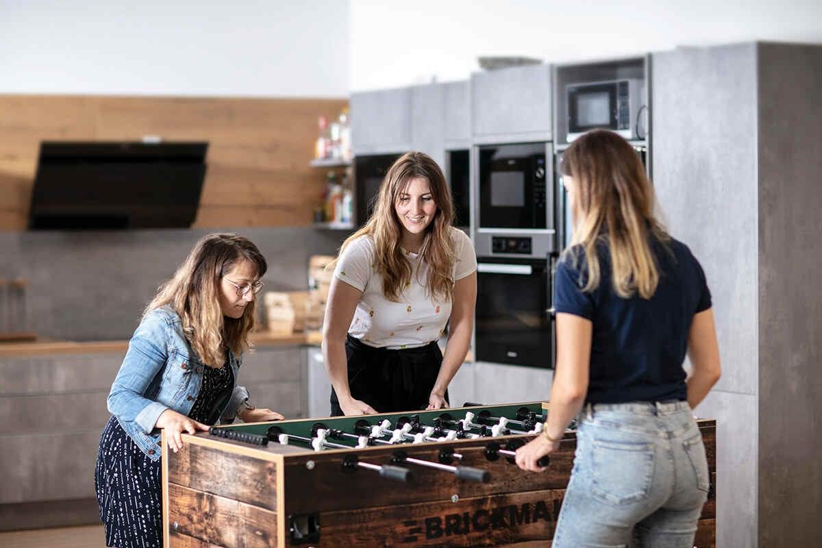 Drei unserer Kolleginnen im Aufenthaltsraum am Kicker spielend.